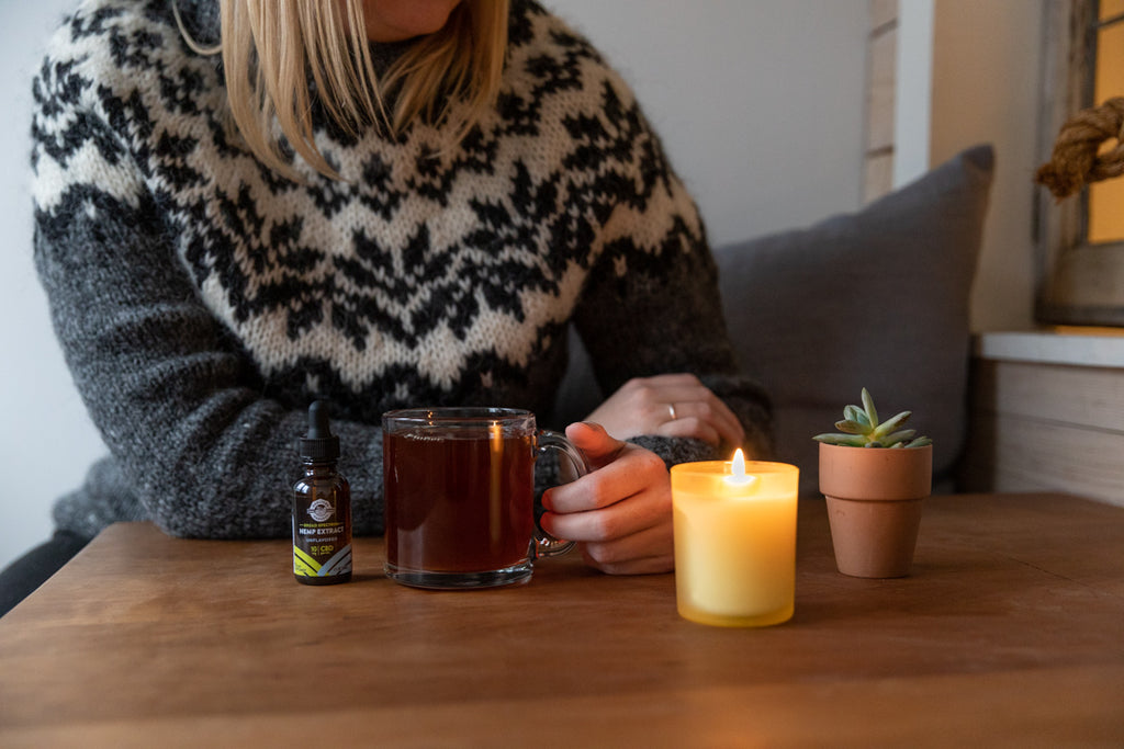 Woman with warm drink and CBD drops