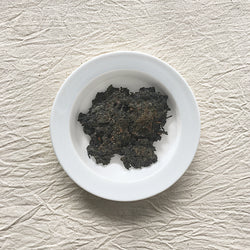 Mansa Tea | Onyx Black | Anhua Blooming Golden Flower Brick - high quality aged dark tea, a type of post-fermented tea from Hunan province, with aging potential of 40-60 years - dark tea on a plate