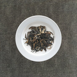 Mansa Tea | Amber Pu'er | Banzhang Raw Pu'er | high quality aged pu'er or pu-erh tea, a type of post-fermented tea from Yunnan province, with aging potential of 40-60 years - image of aged pu'er or aged pu-erh tea on a plate