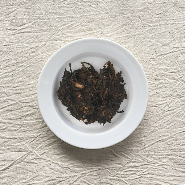 Pasha Ancient Tree Ripe Pu-erh on a plate
