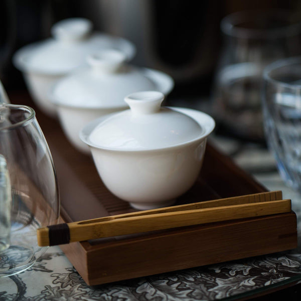White porcelain gaiwan along with other teaware