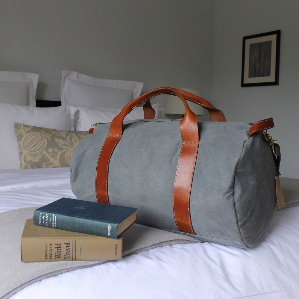 grey weekender bag on the bed
