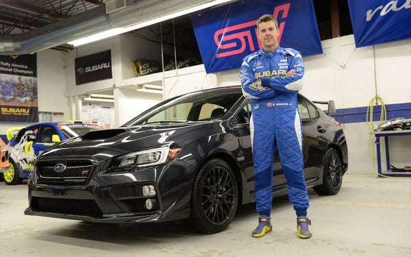 David Higgins stands next to the all new 2015 Subaru STI which he will pilot later in the 2014 Rally America season.
