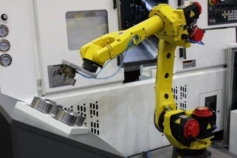 Automated machine loading with a robotic arm
