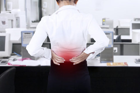Young businesswoman having back pain while working at office