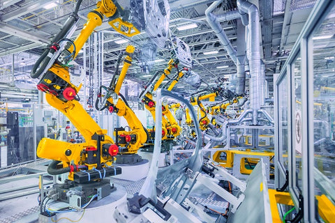 Image of robotic arms in a car plant