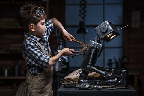 Photo of young boy repairing the robot in the workshop at night