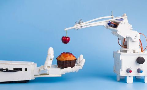 Robot arm technology preparing sweet cupcake with fresh cherry, blue background with free space