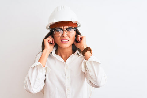 Photo of a young beautiful architect woman covering ears with fingers with an annoyed expression for the noise of loud music