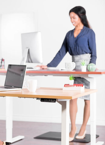 Photo of a woman working on a laptop at a standing desk
