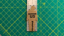 "Load image into Gallery viewer, tiny trump with the slogan ""Danger US"" stuck to a ruler, indicating it is 3 inches tall"
