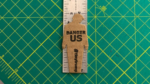 "tiny trump with the slogan ""Danger US"" stuck to a ruler, indicating it is 3 inches tall"