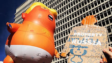 Load image into Gallery viewer, A two foot tall, cardboard tiny trump at a protest held up high next to the trump baby blimp