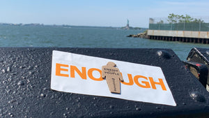 """ENOUGH"" tiny trump sticker measuring 3.75"" x 7.5"" shown stuck to a railing with the Statue of Liberty in the background"