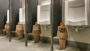 Four, two foot tall, cardboard tiny trumps, each standing next to a urinal in a row of urinals