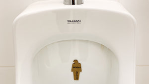 "tiny trump with the slogan ""Sexist"" stuck to a urinal"