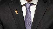 "Load image into Gallery viewer, Closeup of a 1.5"" tall tiny trump enamel pin on a men's suit lapel. tiny trump has a thumbs down sign in the middle of its chest"