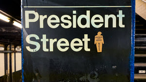 "tiny trump with the slogan ""Putin's Little Bitch"" stuck to a NYC subway sign indicating ""President Street"""