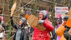 Two protesters marching in the snow, each holding their own two foot tall, cardboard tiny trumps, at the Women's March in New York City