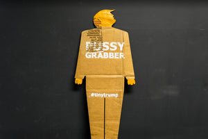 "A two foot tall, cardboard tiny trump with the slogan ""Pussy Grabber"""