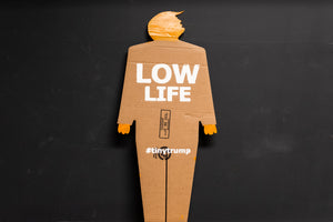 "A two foot tall, cardboard tiny trump with the slogan ""Low Life"""