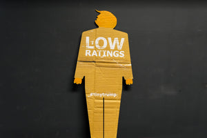 "A two foot tall, cardboard tiny trump with the slogan ""Low Ratings"""