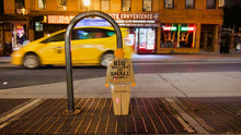 "Load image into Gallery viewer, A two foot tall, cardboard tiny trump with the slogan ""Big Bullies Are Small People"", leaning against a bike rack on the street in New York City"
