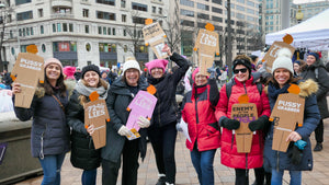 A group of seven protesters at the Women's March in Washington DC holding individual cardboard tiny trumps