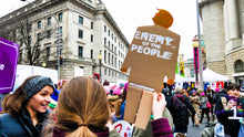 "Load image into Gallery viewer, Protester at a march holding a 2 foot tall, cardboard tiny trump that has ""Enemy of the People"" stamped on it"