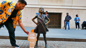 "A two foot tall, cardboard tiny trump with the slogan ""Big Bullies Are Small People"" looking up a the Fearless Girl statue in lower Manhattan"