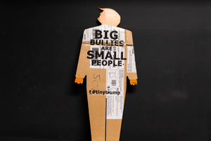 "A two foot tall, cardboard tiny trump with the slogan ""Big Bullies Are Small People"""