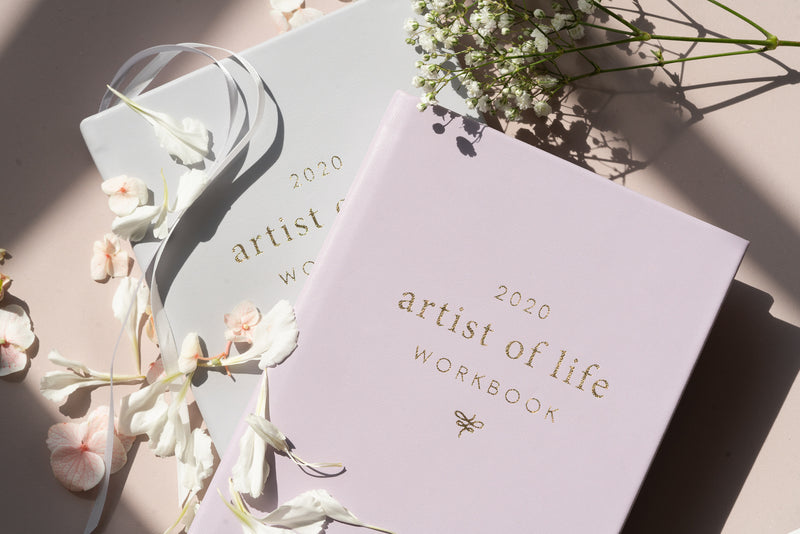 lavender artist of life workbook on top of grey workbook with white flowers, petals, and ribbons resting on top