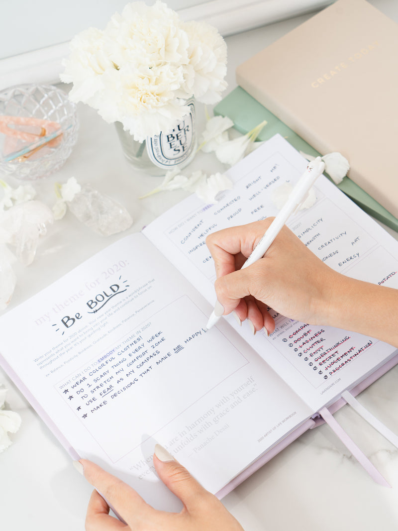 Person writing in lavender artist of life workbook next to Pastel Notebook, Daily Planner, jar with white flowers