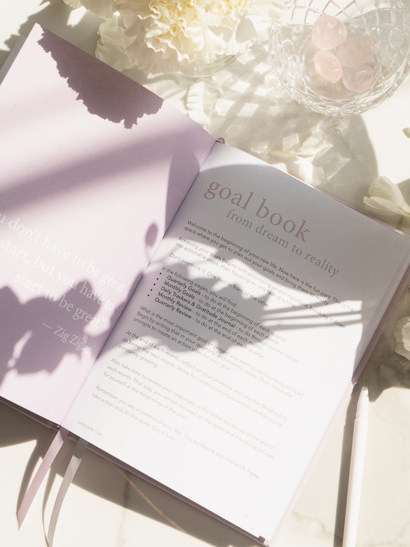 lavender artist of life workbook open to goal book section, next to white flowers and bowl of pink crystals
