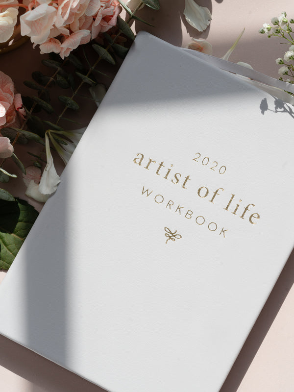 Lavendaire Grey Artist of Life Workbook next to pink and white flowers