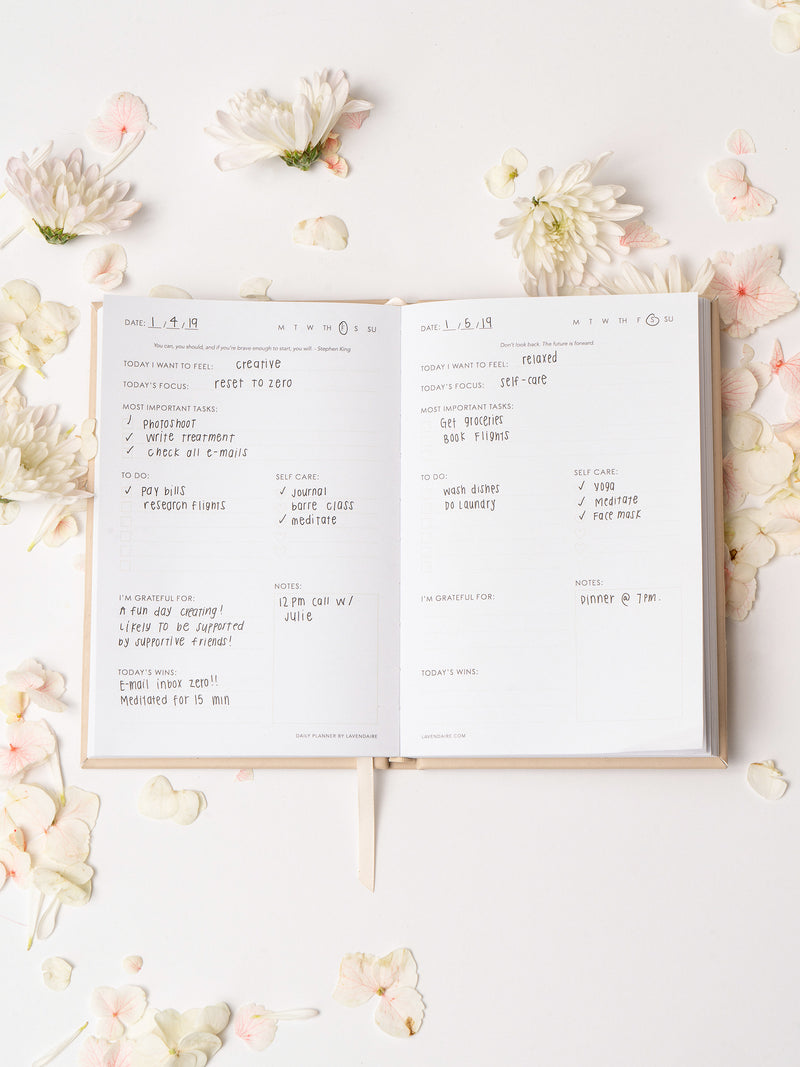 Lavendaire Daily Planner opened with pages filled in surrounded by flower petals