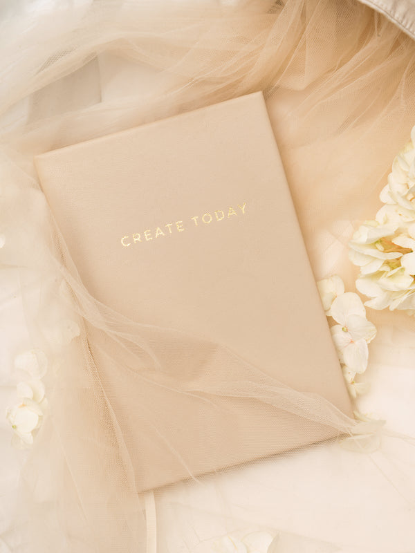 Lavendaire Daily Planner on beige tulle next to flowers