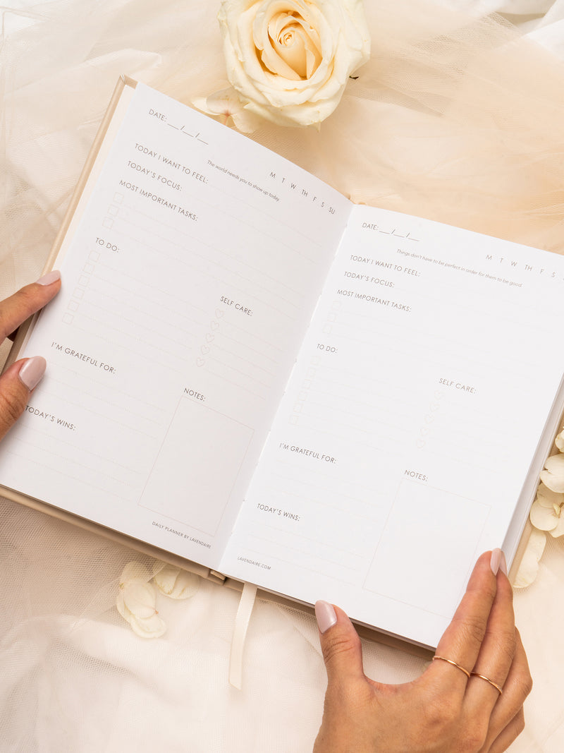 Hands holding Lavendaire Daily Planner open on beige tulle surrounded by flowers
