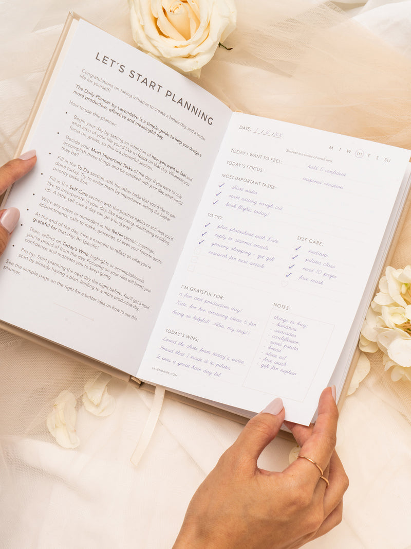Hands open Lavendaire Daily Planner to instruction pages on tulle surrounded by flowers
