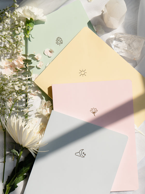 blue, pink, yellow, and green pastel notebooks spread on white background, surrounded by white flowers and white crystals