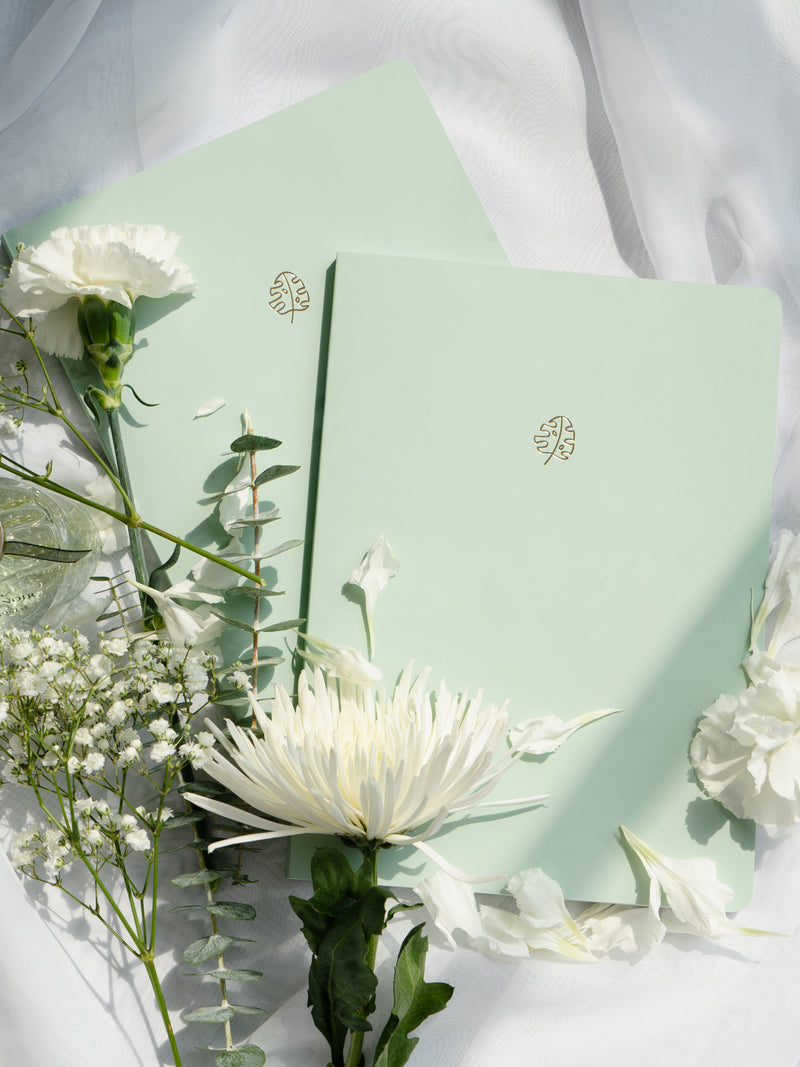 two green pastel notebooks on white fabric background surrounded by white flowers