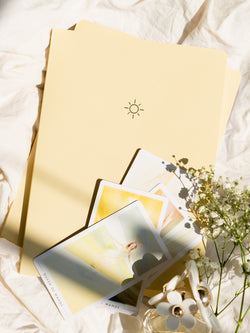 two yellow pastel notebooks on an off-white fabric background, tarot cards resting on top, next to white flowers and perfume bottle