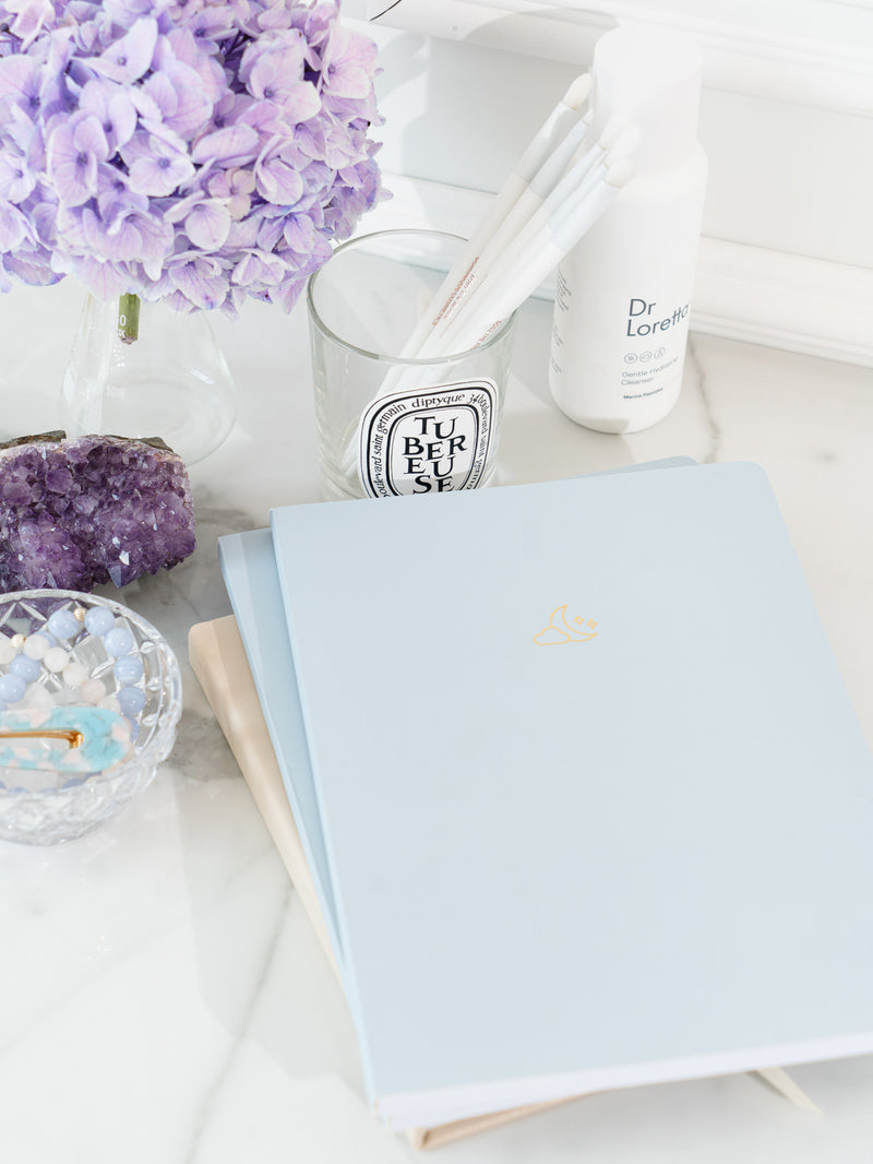 two blue pastel notebooks stacked on top of daily planner on marble surface, next to bowl containing beaded bracelets and blue hair clip, amethyst crystal, jar of lavender flowers, jar of white paint brushes