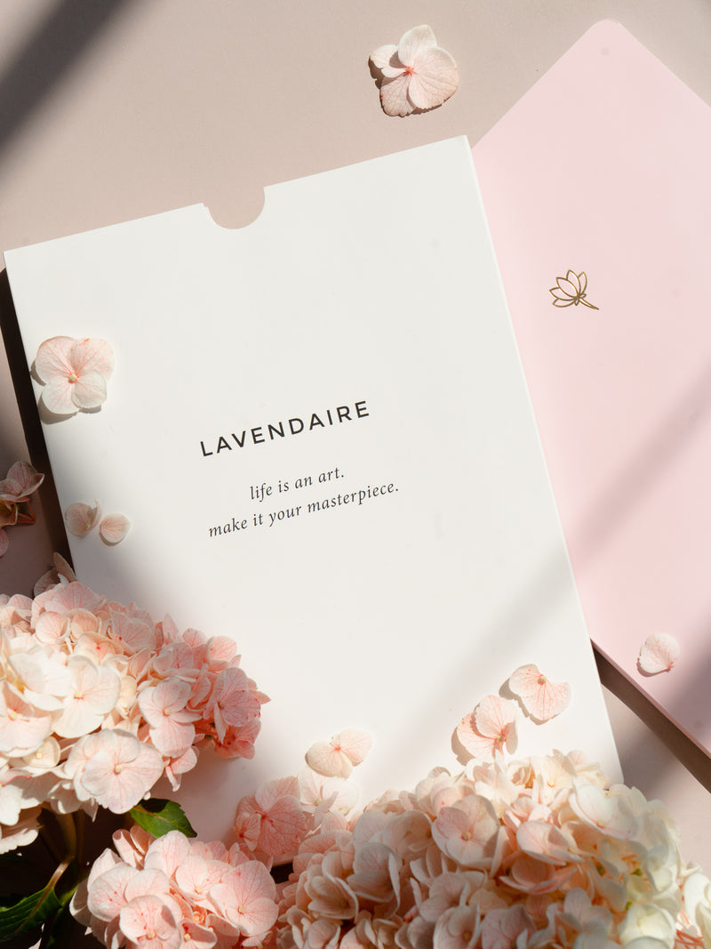 lavendaire pastel notebook sleeve resting on pink pastel notebook with pink flowers and petals resting on top