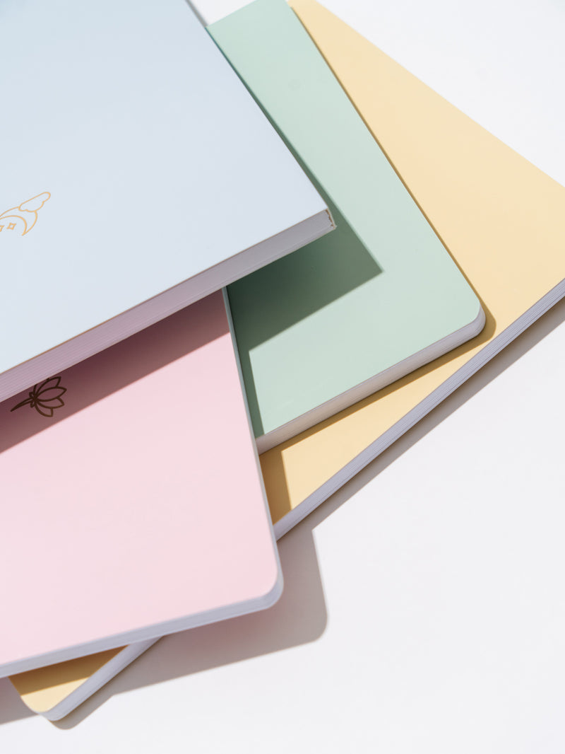 blue, pink, green, and yellow pastel notebooks stacked unevenly on each other, on white surface