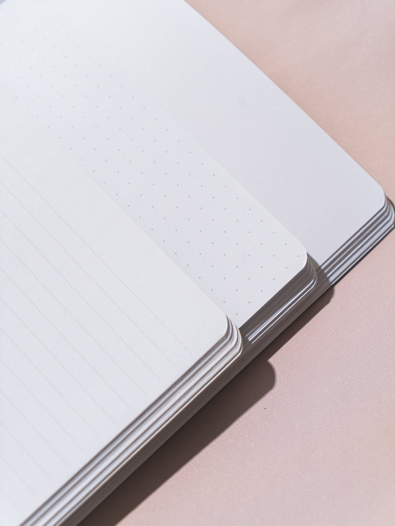 close-up of corners of three pastel notebooks overlapping on pink surface, open to show paper types: blank, lined, dotted