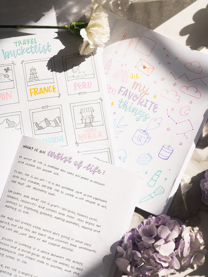 three pastel notebooks open featuring colorful doodles and writing, next to white and purple flowers