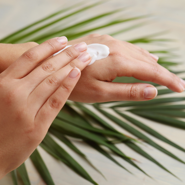 Hand putting on Camel Milk Body Lotion with Tree Leaf Background