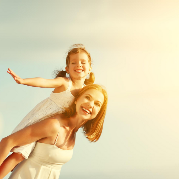 Woman Piggy Backing Daughter in the sun