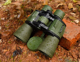 This is a pair of green binoculars that have been photographed in the forest